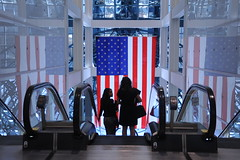 Business women descending the escalator, American flag, reflections on the walls, Chicago, Illinois, USA