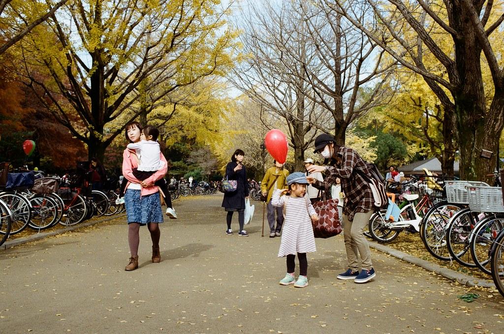 光が丘公園 Tokyo, Japan / Kodak ColorPlus / Nikon FM2 這個畫面也很可愛,是一個小妹妹背包上的氣球纏住她了,但不知道為什麼她媽媽一直在旁邊笑不救她女兒,她女兒就一直快速轉來轉去!  也是很可愛的畫面!  光丘這裡是新社區,看得到很多小朋友與家庭一起出來逛逛的畫面!  很溫馨,尤其是在天氣開始轉涼的季節。  Nikon FM2 Nikon AI AF Nikkor 35mm F/2D Kodak ColorPlus ISO200 7412-0036 2016-11-20 光が丘公園 Tokyo, Japan  Photo by Toomore