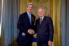 French Foreign Minister Jean-Marc Ayrault shakes hands with U.S. Secretary of State John Kerry after presenting him with the Grand Officer of the Légion d'honneur, the second-highest level of the French award, during a ceremony on December 10, 2016, at the Quai d'Orsay - the French Foreign Ministry - in Paris, France. [State Department Photo/ Public Domain]
