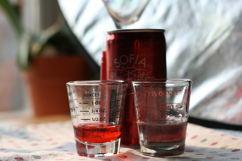 A can of Sofia Blanc de Blancs with a partially full shot glass of red liquid and one of clear liquid.