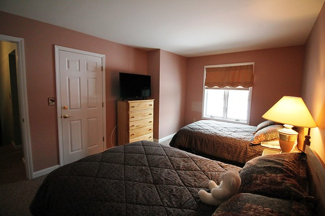 Guest bedroom with two double beds and flat screened TV;