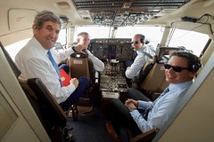 U.S. Secretary of State John Kerry sits with the pilots of  his U.S. Air Force plane on January 18, 2017, as it approached Joint Base Andrews in Camp Springs, Maryland, during the last flight of his tenure as a Cabinet officer after he attended the World Economic Forum in Davos, Switzerland. [State Department photo/Public Domain]