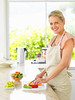Happy woman preparing salad in the kitchen