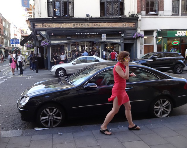 A woman in red passes in Soho