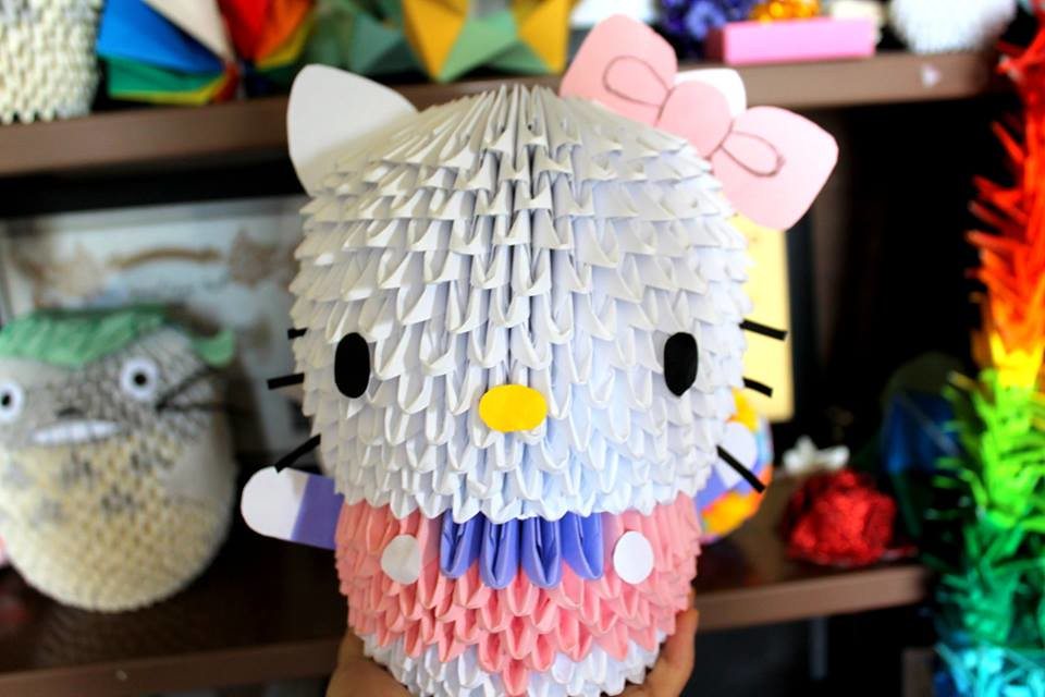A large origami structure of Hello Kitty, with more colourful folded pieces in the shelves in the background. The Hello Kitty structure is made up of many many smaller folded pieces of paper stuck together to create the larger model.