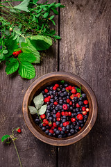 Wooden bowl with wild berries on dark wooden table…