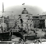 Semi-Circular Quay, Sydney Cove, c1860s, shows a seagoing barque working cargo with the aid of a small steam crane