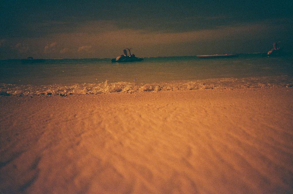 Guam, US / Redscale / Lomo LC-A+ 這張昏昏暗暗的,但我記得那時候沙灘上陽光很強烈,是我不小心撥錯了曝光值嗎?還是陽光也讓 Lomo 很刺眼呢?  朝著海浪的方向、低下身一個盲拍的拍攝,我喜歡 Lomo 這樣不規矩的水平線。  但這張有點像是準備脫離夢境的感覺。  Lomo LC-A+ Lomography Redscale XR 50-200 35mm 6540-0027 2016-11-05 ~ 2016-11-08 Photo by Toomore