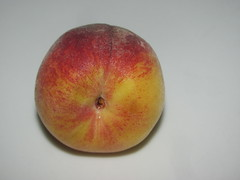 flower(0.0), plant(0.0), macro photography(0.0), produce(0.0), apple(0.0), peach(1.0), fruit(1.0), food(1.0), nectarine(1.0), close-up(1.0),