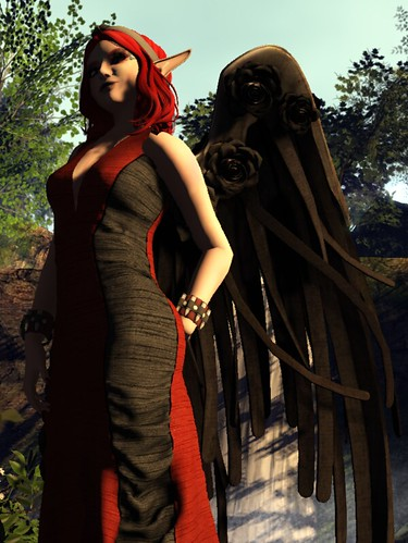 Image Description: Shot angled upward at a figure in a red and black gown, her face in shadow.