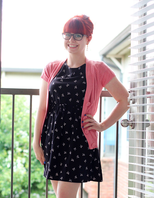 Light Pink Cable Knit Cardigan, Black Bow Print Dress, and a Red Bouffant
