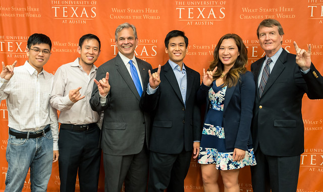 Mayor Steve Adler and President Bill Powers posing with students, alumni and community members