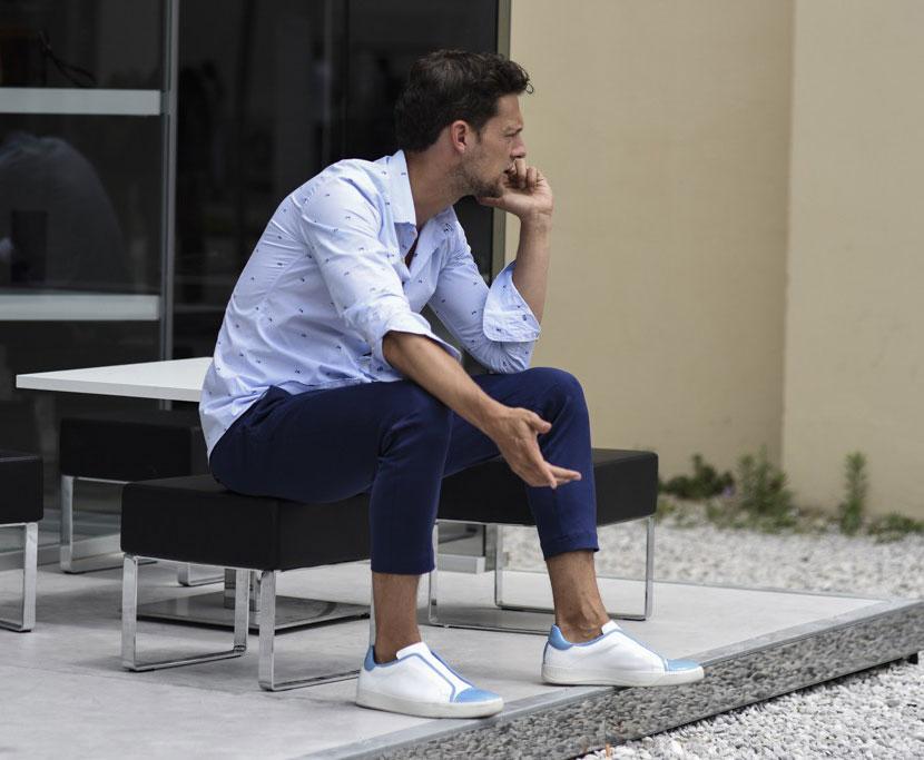 ライトブルーシャツ×紺チノパン×白地に水色パイピングの紐なしスニーカー