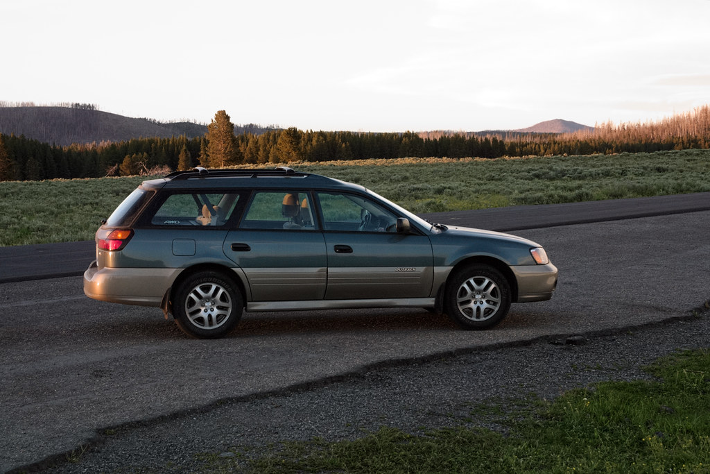 Our 2000 Subaru Outback parked at the trailhead of the Storm Point Trail in Yellowstone
