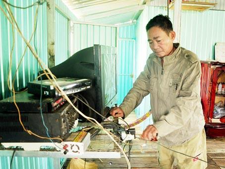 Ông Phạm Lấn bên các thiết bị điện dùng năng lượng mặt trời trong nhà.
