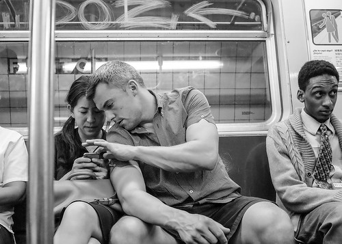 New York City Street Scenes - On the Subway - A Couple Checking Their Phone