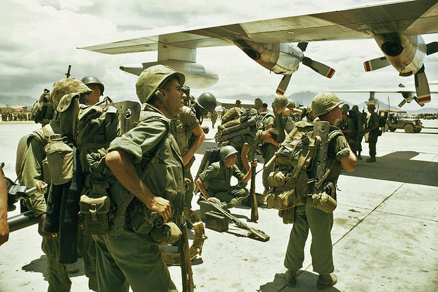 On July 28 1965 fifty thousand US troops were sent to Vietnam. Pictured, United States Marines stand-by on an air base in Da Nang - by Winfield Parks
