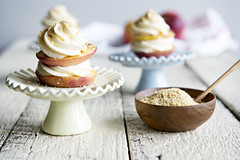 cheesecake peach with frosting on plates on wood table with peaches