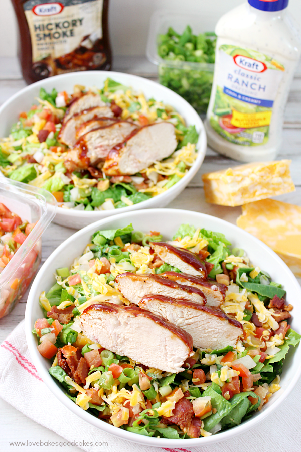 Jacked-Up Monterey Chicken Salad in two bowls with salad dressing and cheese.