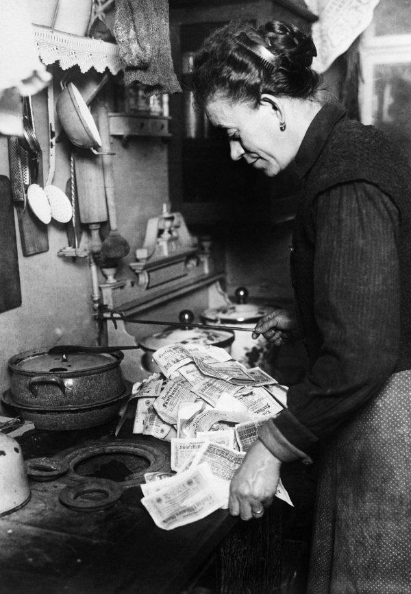 Nemecká žena páli peniaze v kachliach.