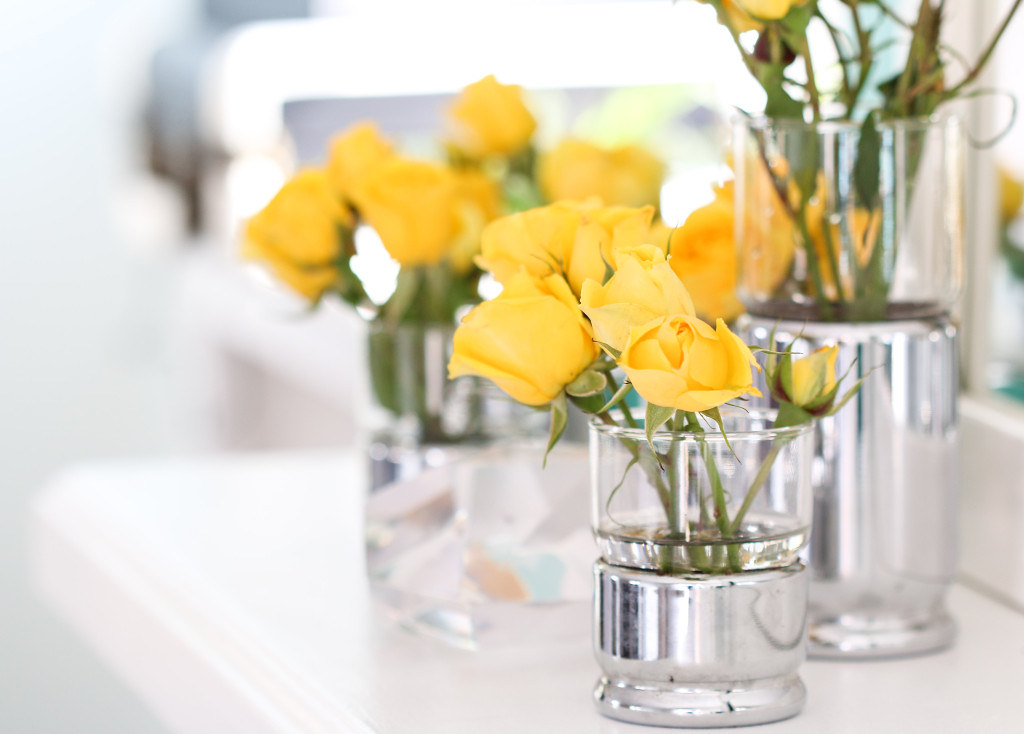 yellow roses in small glass vase on table
