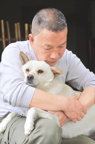 Mr Yang holds his retrieved pet dog Congcong tightly in his arms