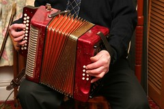 percussion(0.0), string instrument(0.0), hand drum(0.0), wind instrument(0.0), accordion(1.0), diatonic button accordion(1.0), red(1.0), folk instrument(1.0), button accordion(1.0), garmon(1.0), bandoneon(1.0),