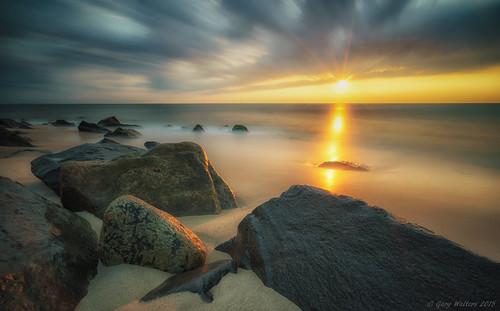 ocean longexposure sky sun beach clouds sunrise outdoors star newjersey rocks sony sandy shore dreamy serene hook tranquil sandyhook sunstar sel1635z