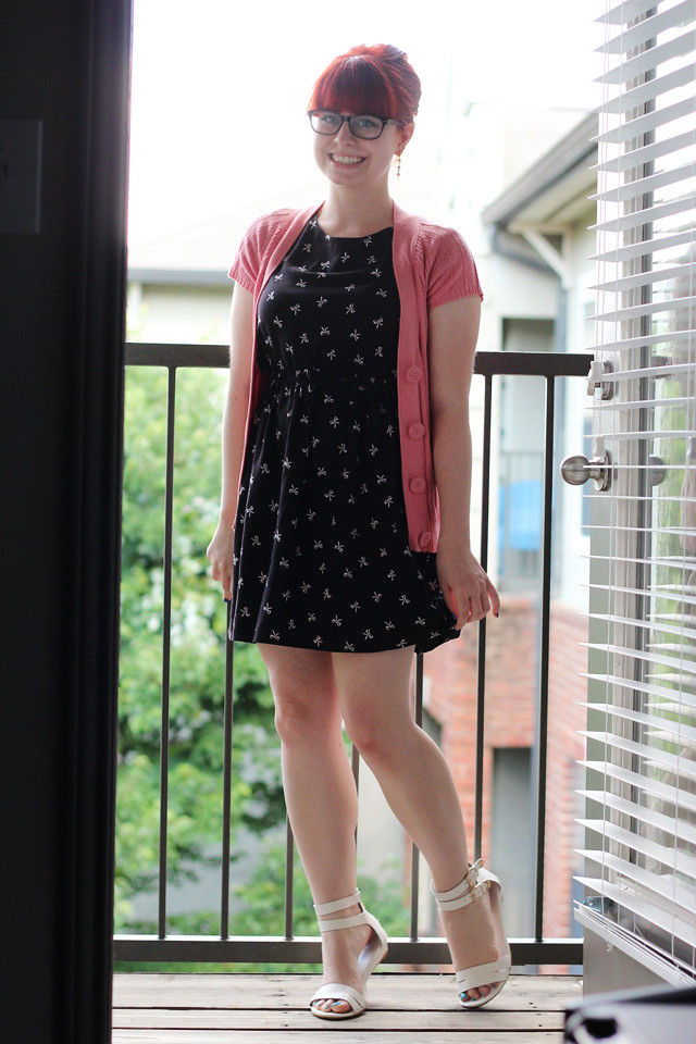 Black Bow Print Dress, Pink Short Sleeved Cardigan, White Sandals, and a Bouffant