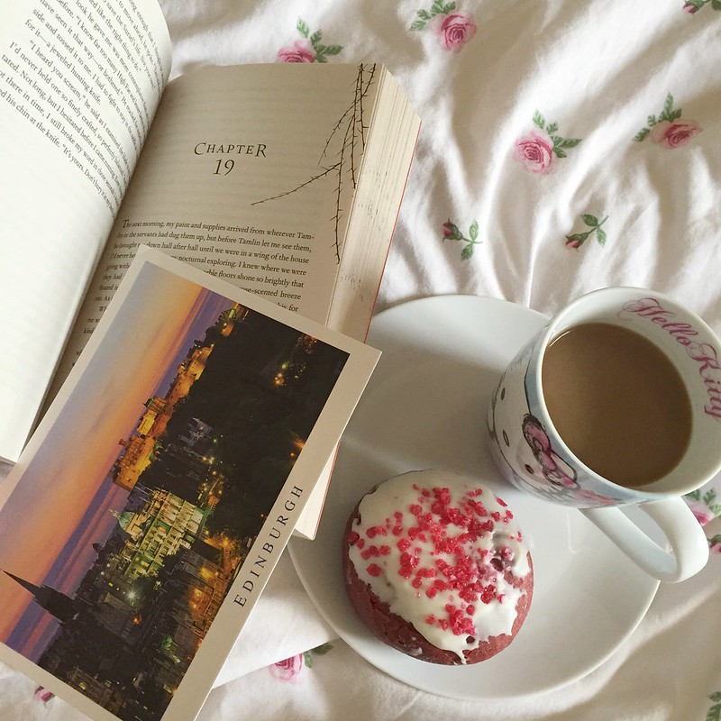 Coffee, a doughnut, and a book in bed