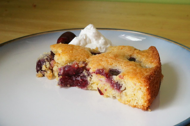 Light and airy cherry cake, plated with whipped cream and a cherry garnish