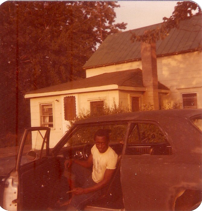 A man in a white shirt sits in a black Chevy. There's a small house and trees in the background.