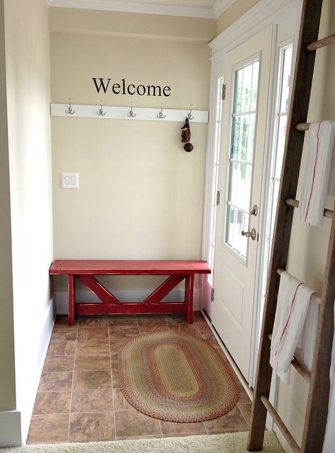 red bench and coat hooks in the entry way