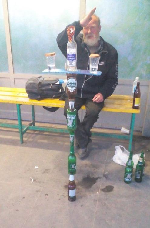 imagen graciosa de hombre rezando a una cruz de botellas