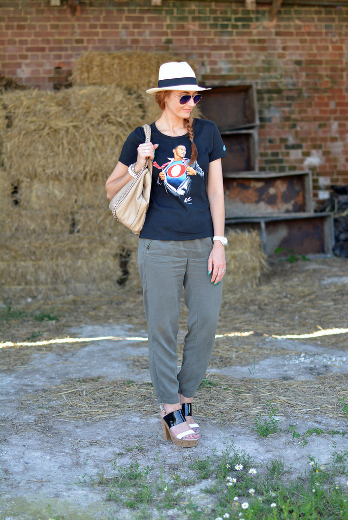 Black graphic tee with Panama hat, khaki track pants, strappy platforms