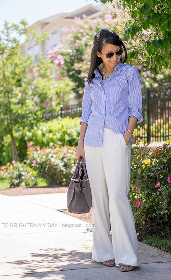 green necklace, blue striped button up shirt, white pants, gray tote