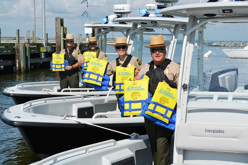 Photo of Natural Resource Police boat patrol holding up life jackets