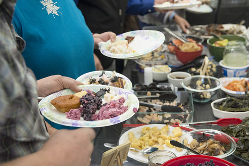 Participants in the Dena'ina Wellness Center's monthly Native Foods Potluck prepare their plates with traditional foods from around the state.