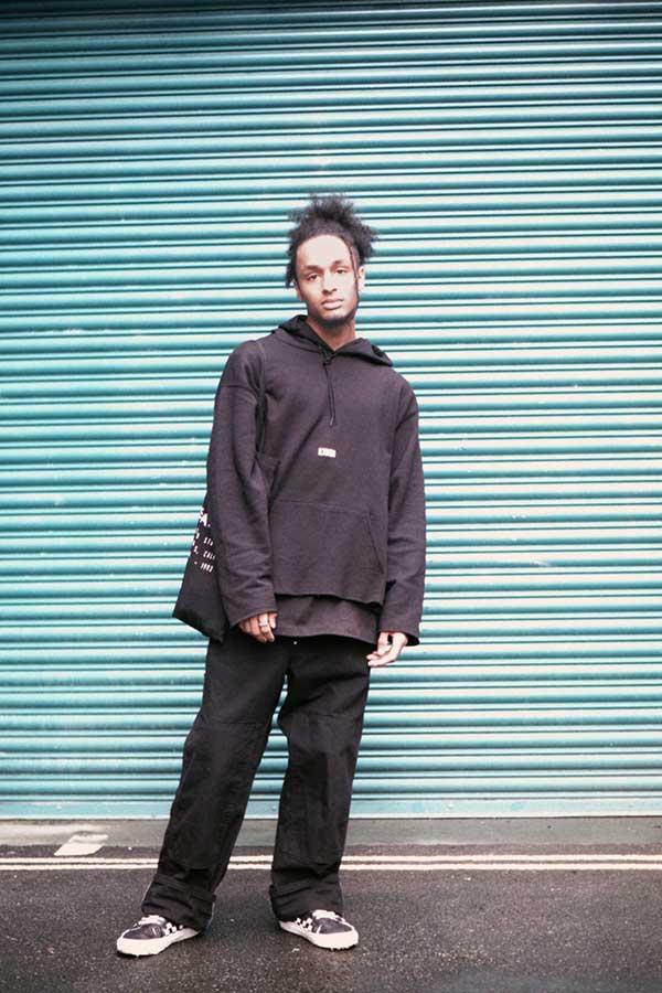 黒プルオーバーパーカー×黒ロング丈Tシャツ×黒ワイドパンツ×VANS OLD SKOOLチェッカーフラッグ