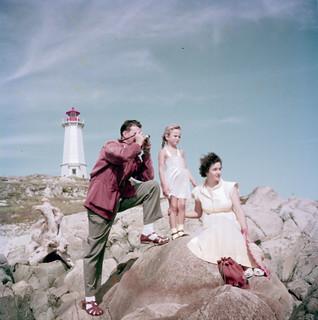 Man, woman and little girl on the rocks below the lighthouse at Fortress of Louisbourg National Historic Site... / Un homme, une femme et une petite fille sur des rochers, près du phare, dans le lieu historique national de la Forteresse de Louisbourg