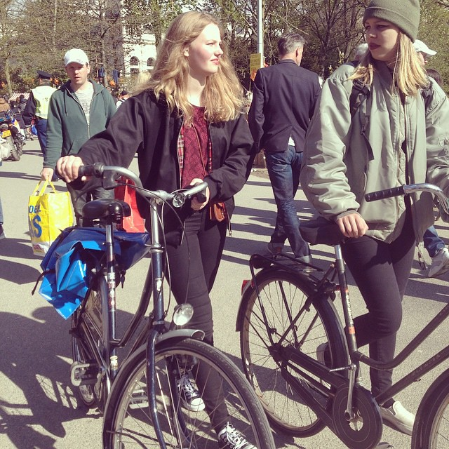 Having a chat while walking your bike. It s cold again so some people get extremely prudent and wear winter clothes again! No worries sun should be back by the end of the week #sunshine #summerinthecity #bikeams #bici #bike #velo #cyclechic