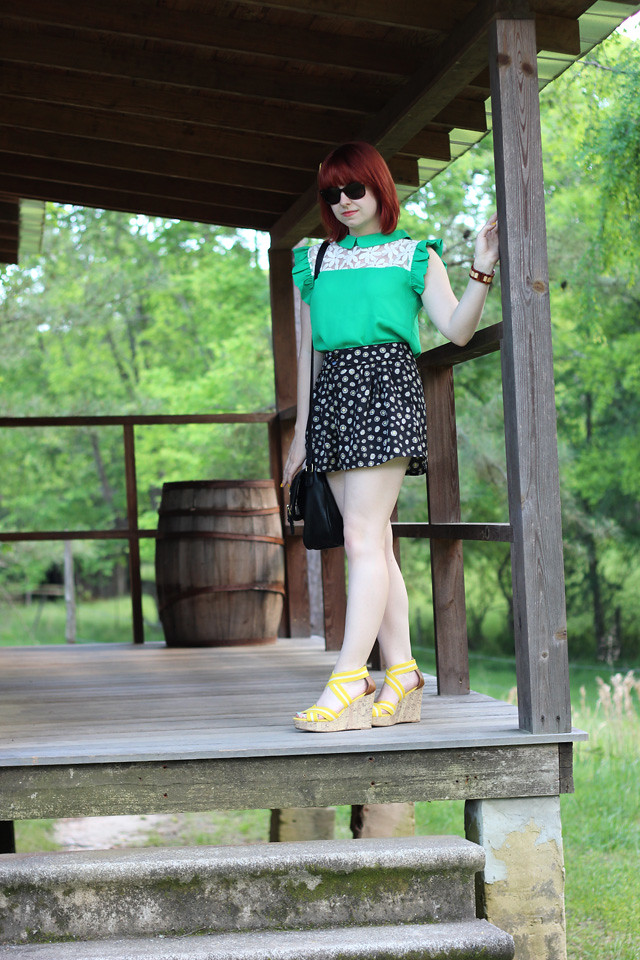 Green Top with Ruffle Sleeves and Floral Neckline, Black Patterned Shorts, and Yellow Wedge Sandals