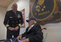 Rear Adm. Bret Muilenburg presents a coin to retired Carpenter's Mate 1st Class Macy Coffin, a World War II Seabee veteran, following the Seabees 75th anniversary kickoff ceremony.  (U.S. Navy/MCC Lowell Whitman)