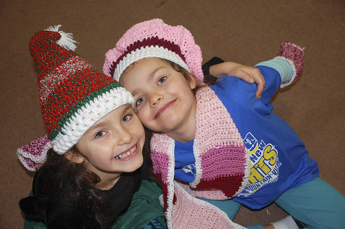Twins Esther and Maya Kaliberda show off hats and scarves knitted at Wildwood for children at the Early Childhood Center.