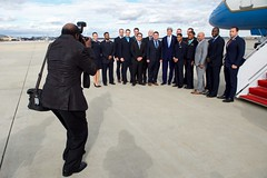 U.S. Secretary of State John Kerry poses for a photo with the crew of his U.S. Air Force plane on January 18, 2017, after it landed at Joint Base Andrews in Camp Springs, Maryland, following the last flight of his tenure as a Cabinet officer after he attended at the World Economic Forum in Davos, Switzerland. [State Department photo/Public Domain]