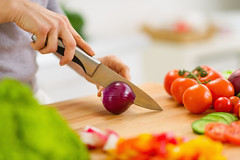 Closeup on housewife cutting red onion