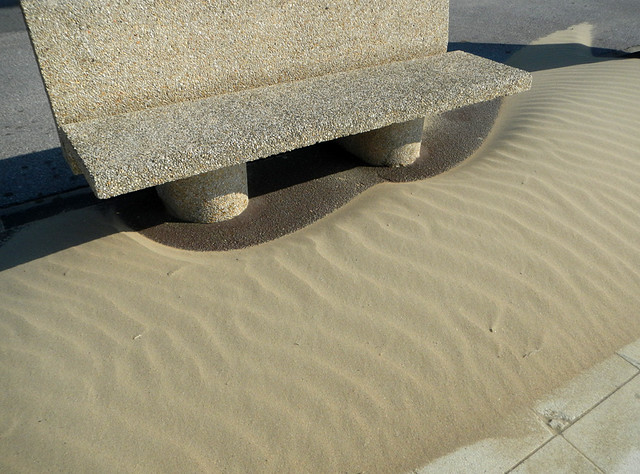 Wind-blown sand piling up around a bench at Petit Fort Philippe on the north coast of France