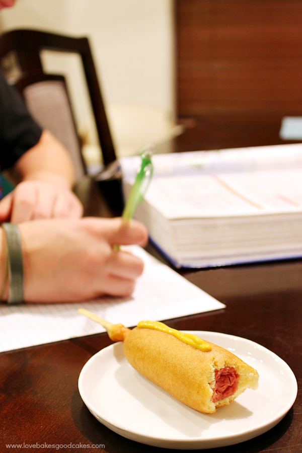 A corn dog on a white plate with mustard.