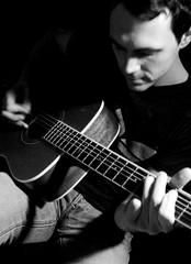 slide guitar(0.0), bass guitar(0.0), bassist(1.0), string instrument(1.0), musician(1.0), music(1.0), acoustic guitar(1.0), monochrome photography(1.0), guitarist(1.0), guitar(1.0), jazz guitarist(1.0), monochrome(1.0), black-and-white(1.0), black(1.0), string instrument(1.0),