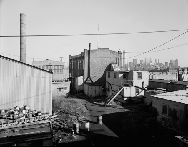 Another tip of the hat to my Jersey City friends. Before Liberty State Park, the JC shoreline consisted of lots of abandoned railroad land. A view of the Central Railroad of NJ machine shops, sheds and Pier 19. Ellis Island is at right. March 1975